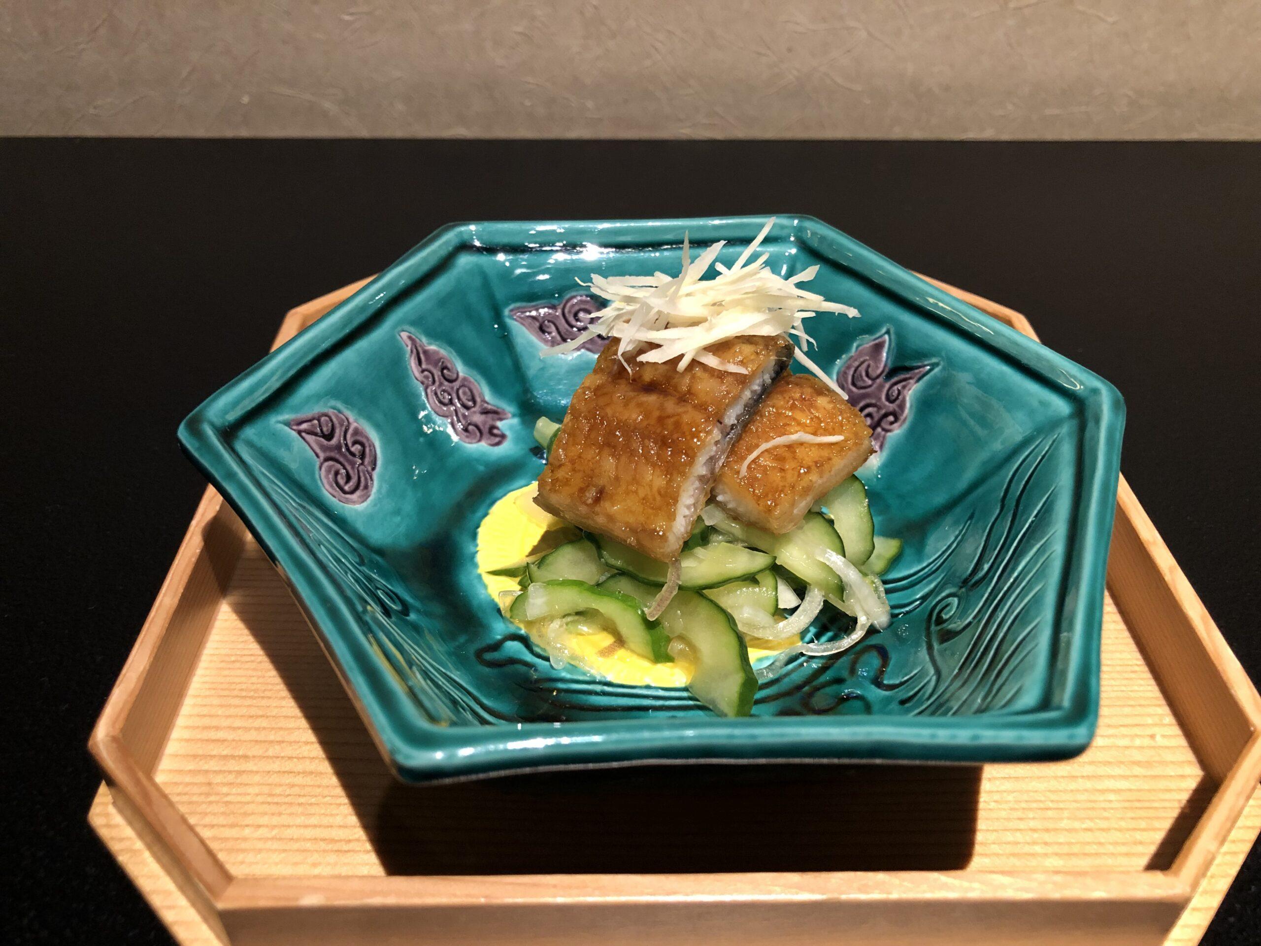 【日本料理みつわ】本日の一皿<p>鰻の蒲焼きを 冷やしたきゅうりの酢の物と一緒にいただく「鰻ざく」 柔らかく旨味たっぷりの鰻と、 シャキシャキとした食感のきゅうりは 味と食感のコントラストが絶妙。 暑い夏にさっぱりといただける一皿です。</p>
